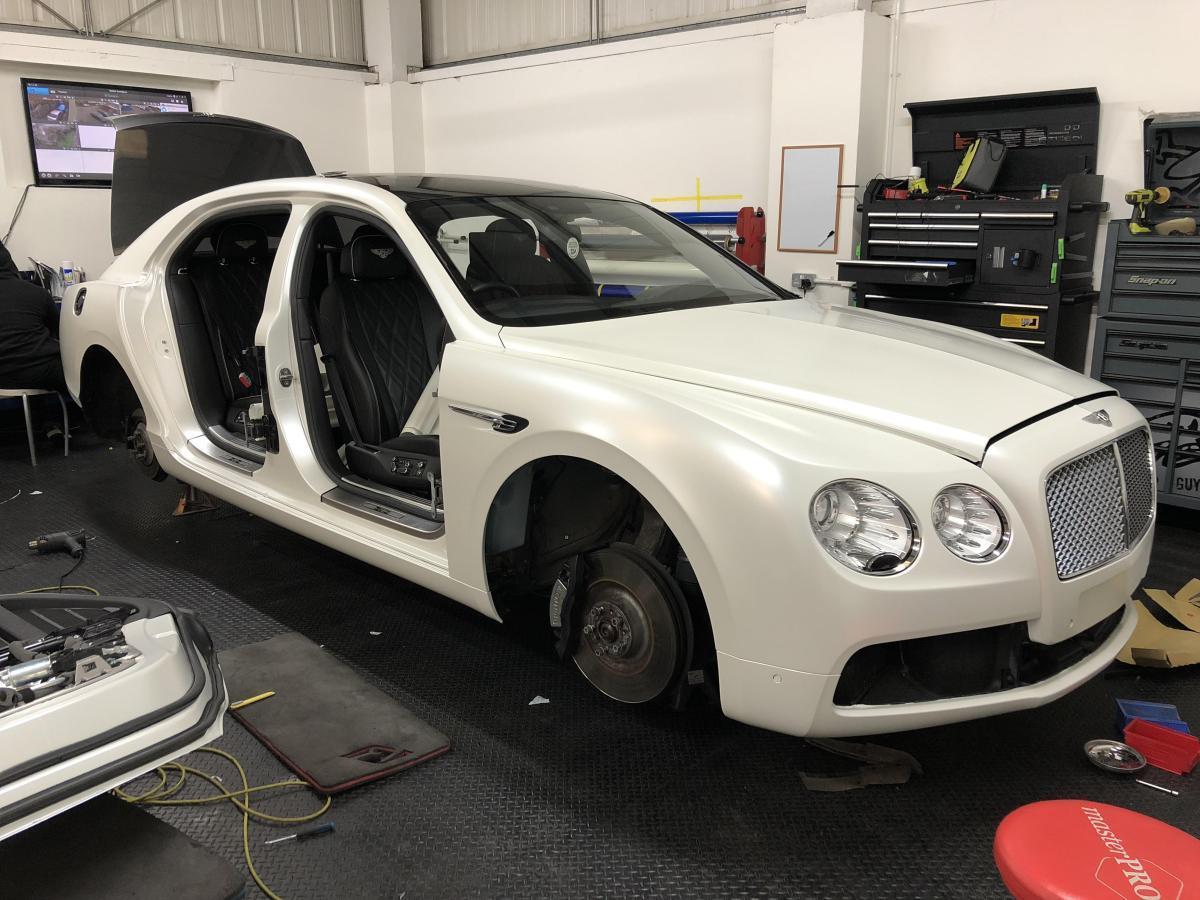 Car wrapping door shuts on a Bentley